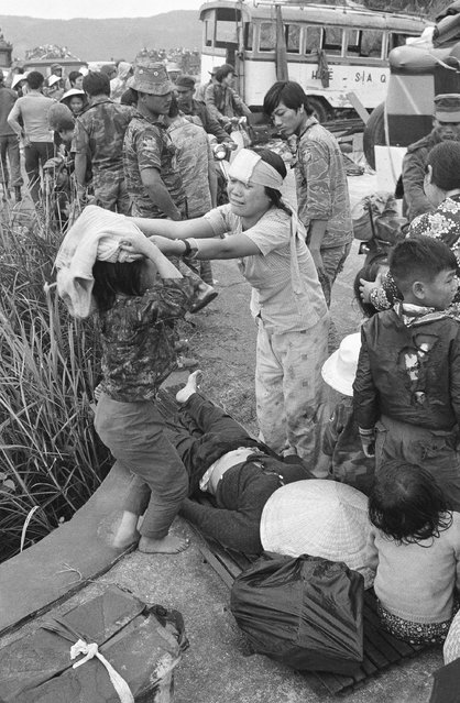 Injured victims of a road accident in the panicky flight from Hue stand over a dead woman in Hai Van Pass, March 21, 1975. Fatal accidents and injuries were common among the thousands of refugees who fled advancing North Vietnamese, and attempted to find refuge in the coastal city of Da Nang. (Photo by AP Photo)