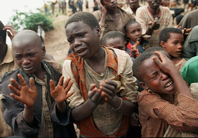 In this August 20, 1994, file photo, Rwandan refugee children plead with Zairean soldiers to allow them across a bridge separating Rwanda and Zaire where their mothers had crossed moments earlier before the soldiers closed the border, in Zaire, now known as Congo. Twenty-five years ago Rwanda descended into violence in which some 800,000 Tutsis and moderate Hutus were massacred by the majority Hutu population over a 100-day period in what was the worst genocide in recent history. (Photo by Jean-Marc Bouju/AP Photo/File)