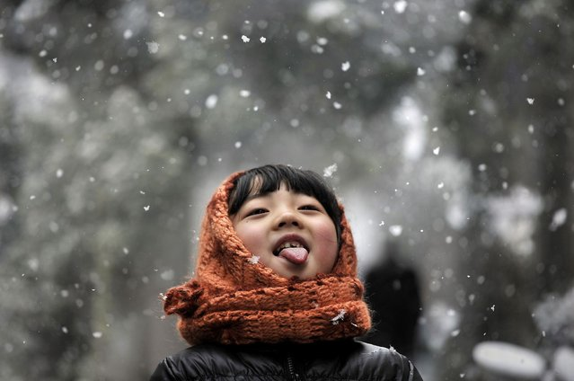 A girl sticks out her tongue during snowfalls on a street in Hefei, Anhui province February 13, 2014. (Photo by Reuters/Stringer)