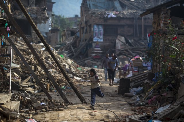 An earthquake survivor run past collapsed houses in Sankhu, on the outskirts of Kathmandu, Nepal, May 5, 2015. (Photo by Athit Perawongmetha/Reuters)