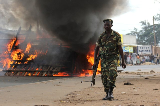 A soldier walks past a barricade erected on the road by demonstrators protesting against the ruling CNDD-FDD party's decision to allow Burundian President Pierre Nkurunziza to run for a third five-year term in office, in Bujumbura, May 7, 2015. (Photo by Jean Pierre Aime Harerimana/Reuters)