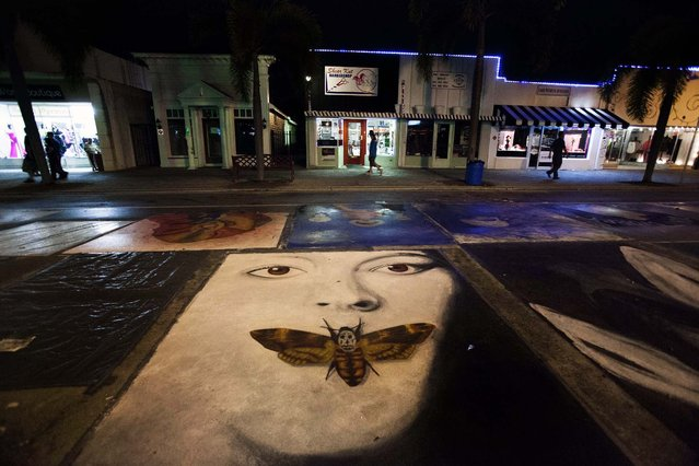 Saturday night, some paintings ae covered and others remain exposed to the elements on Lake Ave. (Photo by Mark Edelson/The Palm Beach Post)