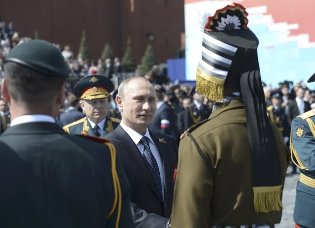 Russia's President Vladimir Putin (C) shakes hands with a parade participant after the Victory Day parade at Red Square in Moscow, Russia, May 9, 2015. (Photo by Reuters/Host Photo Agency/RIA Novosti)
