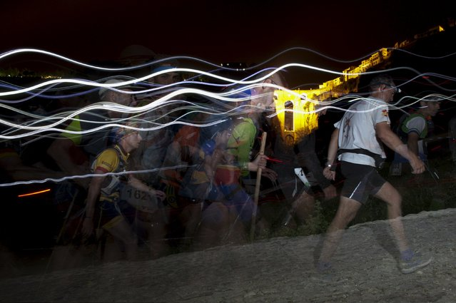 "Trails of headlamps are seen in the night as runners and a mountain biker make their way to the finish line, in front of ""Puente Nuevo"" (New Bridge), as they participate in the XVIII 101km international competition in Ronda, southern Spain, May 10, 2015. (Photo by Jon Nazca/Reuters)"