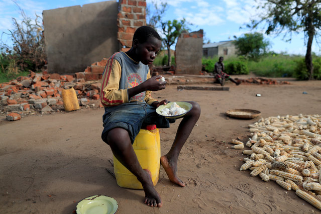 """Bernado Jofresse, 14, eats rice for breakfast as he sits beside his family's damaged house in the aftermath of Cyclone Idai, in the village of Cheia, which means """"Flood"""" in Portuguese, near Beira, Mozambique April 3, 2019. (Photo by Zohra Bensemra/Reuters)"""