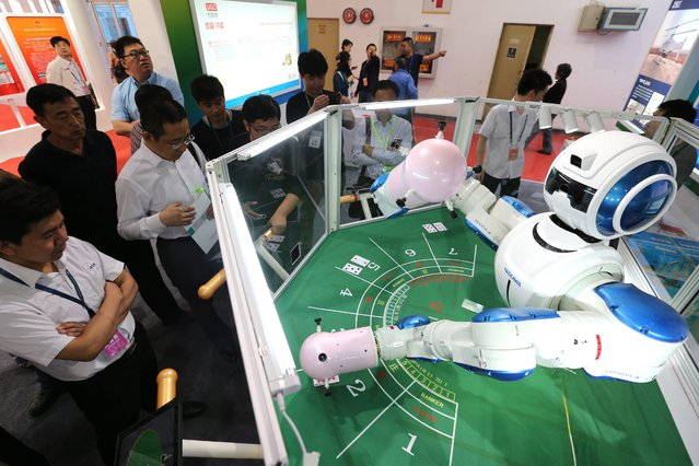 Visitors look at a robot serving for cards games at the 18th China Beijing International High-Tech Expo in Beijing, China, 13 May 2015. The expo runs from 13 to 17 May at the China International Exhibition Center displaying high-tech products coming from as many as 1,600 domestic and foreign enterprises. (Photo by Wu Hong/EPA)