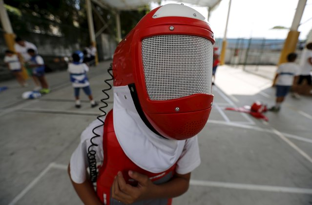 """A child from municipal school Parana poses for a photograph during the project """"Fencing School"""" in Rio de Janeiro, Brazil, March 30, 2016. (Photo by Sergio Moraes/Reuters)"""