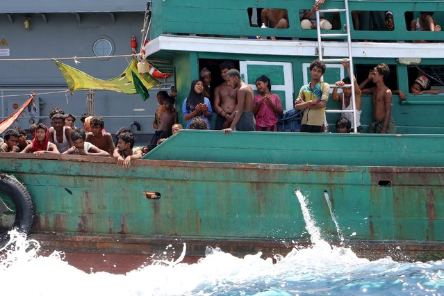 Migrants react from their boat as they are towed away from Thailand by a Thai navy vessel, in waters near Koh Lipe island May 16, 2015. (Photo by Aubrey Belford/Reuters)