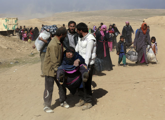 Tired displaced Iraqis flee their homes due to fighting between Iraqi security forces and Islamic State militants, on the western side of Mosul, Iraq, Sunday, February 26. 2017. (Photo by Khalid Mohammed/AP Photo)