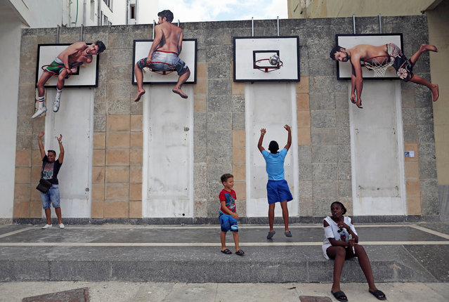 Children play basketball with an installation by Spanish artists Martin and Sicilia during the 13th Havana Biennial, in Havana, Cuba on April 12, 2019. (Photo by Fernando Medina/Reuters)
