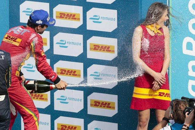 Brazil's Luca di Grassi of the Audi Sport Abt racing team sprays  on a volunteer as he celebrates after winning the Formula E Berlin ePrix auto race at the former airport Tempelhof, in Berlin, Germany, Saturday, May 23, 2015.  (Photo by Markus Schreiber/AP Photo)