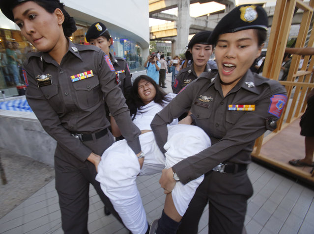 Police officers carry a student protester in Bangkok, Thailand Friday, May 22, 2015. (Photo by Sakchai Lalit/AP Photo)
