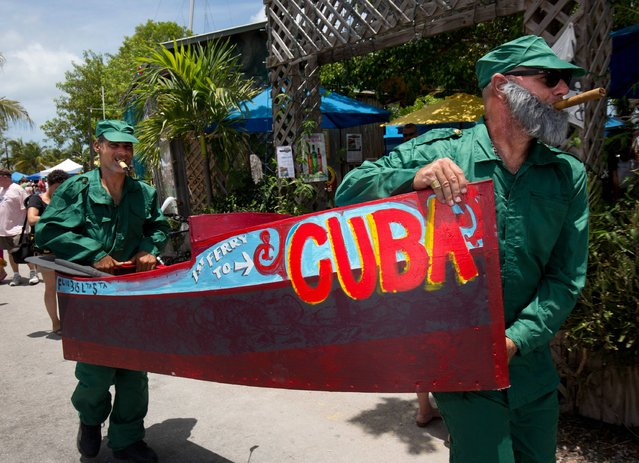 Abel Garcia, (L), portraying Cuban President Raul Castro, and Buck McQuire, dressed as Fidel Castro, carry their Schooner Wharf Minimal Regatta entry to the water in Key West Florida in this May 24, 2015 handout photo. (Photo by Rob O'Neal/Reuters/Florida Keys News Bureau)