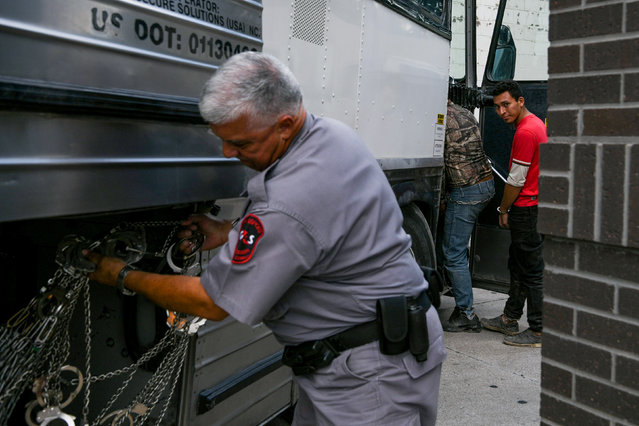 Shackled migrants in federal custody are loaded onto a bus following immigration hearings at the U.S. federal courthouse in McAllen, Texas, U.S., June 28, 2019. (Photo by Loren Elliott/Reuters)