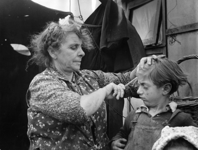 A Romany woman combing her son's matted hair outside her tent in an encampment on Corke's Meadow, Kent on 28th July 1951. (Photo by Bert Hardy/Picture Post/Getty Images)