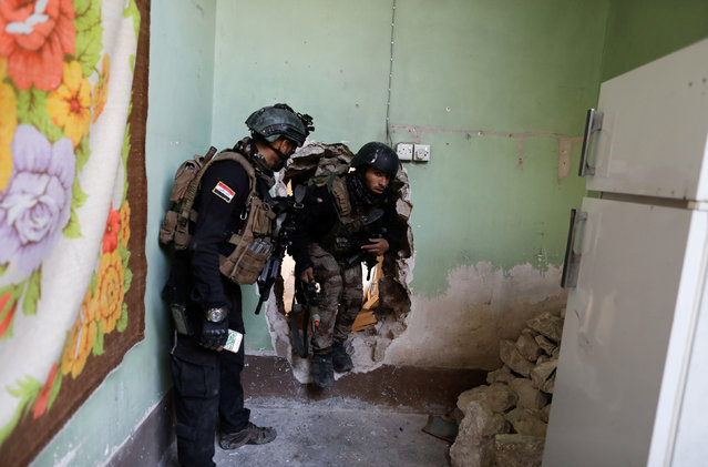 A Special forces member enters a house through a hole in a wall during a battle with Islamic State militants in western Mosul, Iraq March 7, 2017. (Photo by Zohra Bensemra/Reuters)