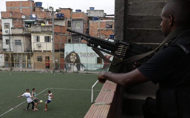 Boys play soccer as a policeman patrols one day after the occupation of the Mare slums complex in Rio de Janeiro, March 31, 2014. (Photo by Ricardo Moraes/Reuters)