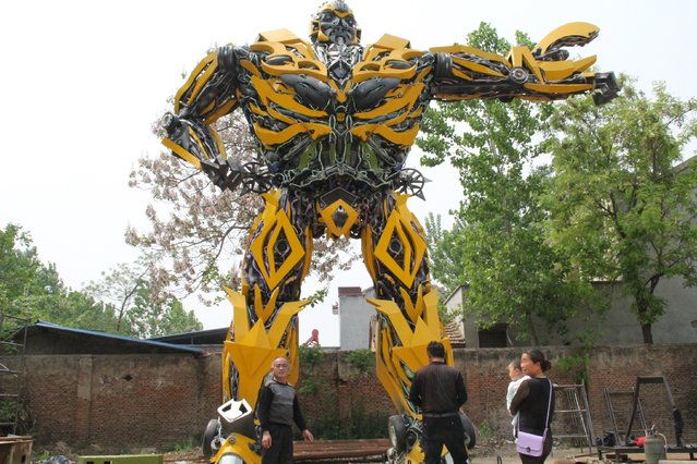 """People look at a replica of a """"Transformer"""", made by a fan, in Shangqiu, Henan Province, China, April 22, 2016. According to local media, the owner took a year to build the replica, which is made of vehicle components and weighted about 17 tons. (Photo by Reuters/Stringer)"""