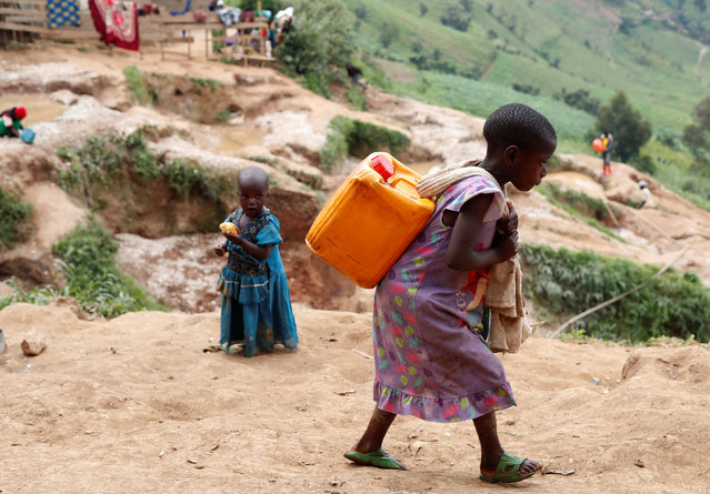 A girl carries a container of water at a coltan mine in Kamatare, Masisi territory, North Kivu Province of Democratic Republic of Congo on December 17, 2018. (Photo by Goran Tomasevic/Reuters)