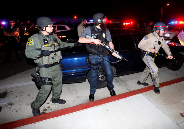 Police in riot gear arrive to break-up a demonstration outside Republican U.S. presidential candidate Donald Trump's campaign rally in Costa Mesa, California, April 28, 2016. (Photo by Mike Blake/Reuters)