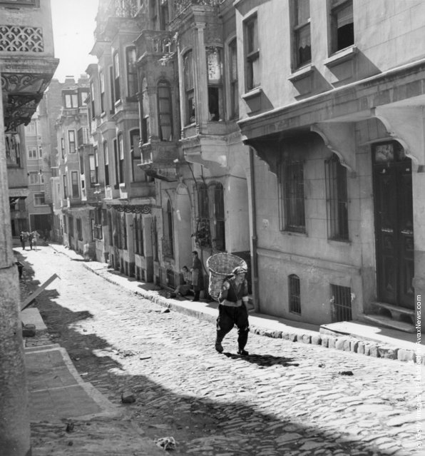 1957: An old man carrying a large basket walks down a narrow cobbled street in what is by night Istanbul's main area for prostitution