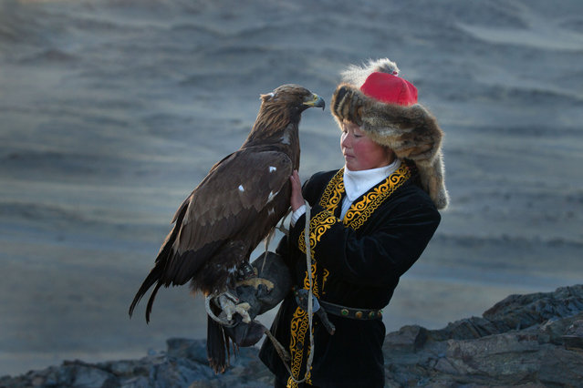 13 year old Ashol Pan with her eagle – Despite her young age, Ashol had the amazing ability to control and be able to caress her eagle, almost as if she had been with it for years. (Photo by Asher Svidensky/Caters News)