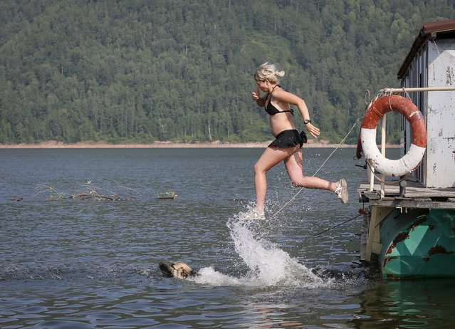 A woman and her German Shepherd cool off in the Yenisei River at air temperature about 32 degrees Celsius (90 degrees Fahrenheit) outside the Siberian city of Krasnoyarsk, Russia, July 2, 2015. (Photo by Ilya Naymushin/Reuters)
