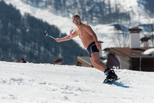 A man dressed in a swimsuit participates in the BoogelWoogel alpine carnival at the Rosa Khutor Alpine Resort in Krasnaya Polyana, Sochi, Russia on April 1, 2017. (Photo by Artur Lebedev/TASS)