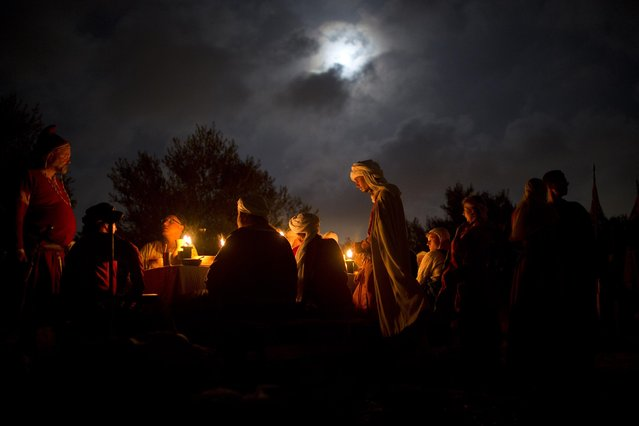 In this Thursday, July 2, 2015 photo, Israeli and Russian members of knight clubs wearing medieval costumes eat dinner two nights before marching 27 kilometers (17 miles) to the reenactment of the Battle of Hattin from the ancient Israeli city of Zippori to Horns of Hattin, northern Israel. (Photo by Oded Balilty/AP Photo)