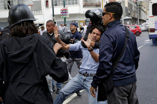 A pro-government supporter wearing a helmet grabs an opposition supporter during a protest against Venezuelan President Nicolas Maduro's government outside the Venezuelan Prosecutor's office in Caracas, Venezuela on March 31, 2017. (Photo by Marco Bello/Reuters)