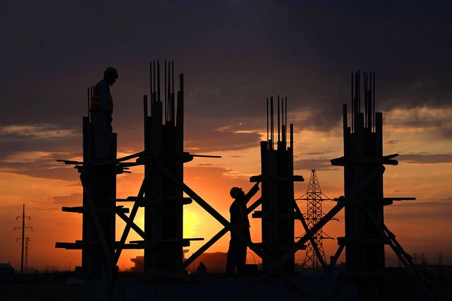 Afghan labourers work at a construction site during sunset in Mazar-i-Sharif on April 22, 2014. Afghanistan remains at war, with civilians among the hardest hit as the Taliban wage an increasingly bloody insurgency against the government. (Photo by Farshad Usyan/AFP Photo)