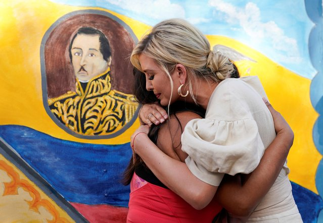 """With an image of """"El Liberator"""" Simon Bolivar on a mural behind, White House adviser Ivanka Trump hugs a migrant woman during a visit a center for Venezuelan migrants in Cucuta, Colombia, September 4, 2019. (Photo by Kevin Lamarque/Reuters)"""