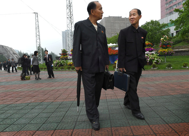 Two Korean men walk and chat in Pyongyang, North Korea on May 6, 2016. (Photo by Linda Davidson/The Washington Post)