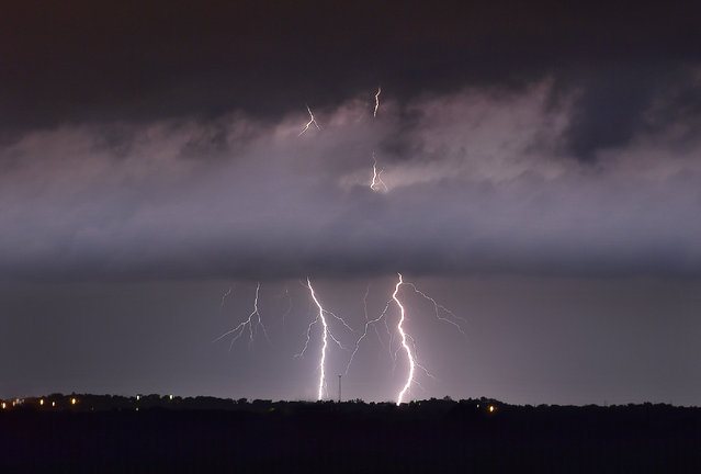In this Wednesday, May 20, 2015 photo, lightning strikes between the towns of Krum and Sanger in Denton County, Texas, as a tornado warning was in effect for Sanger, Bolivar and Krum just after midnight. (Photo by Al Key/The Denton Record-Chronicle via AP Photo)
