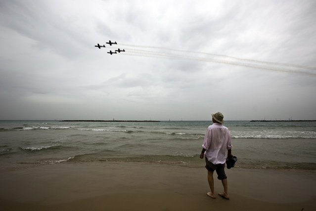 A man watches Israeli Air Force planes fly over the Mediterranean Sea from a beach at Tel Aviv during an aerial show as part of celebrations for Israel's Independence Day to mark the 66th anniversary of the creation of the state, May 6, 2014. (Photo by Nir Elias/Reuters)