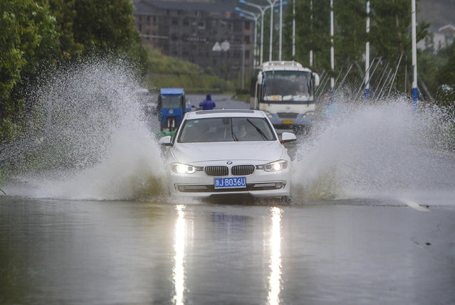 In this photo provided by China's Xinhua News Agency, cars run on a road submerged by water in Sanmen county,  east China's Zhejiang Province, Saturday, July 11, 2015. (Photo by Xu Yu/Xinhua News Agency via AP Photo)