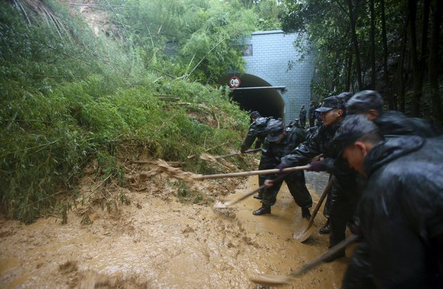 Soldiers clean up at a landslide site blocking a tunnel amid heavy rainfall under the influence of Typhoon Chan-hom, in Ningbo, Zhejiang province, China, July 11, 2015. (Photo by Reuters/Stringer)