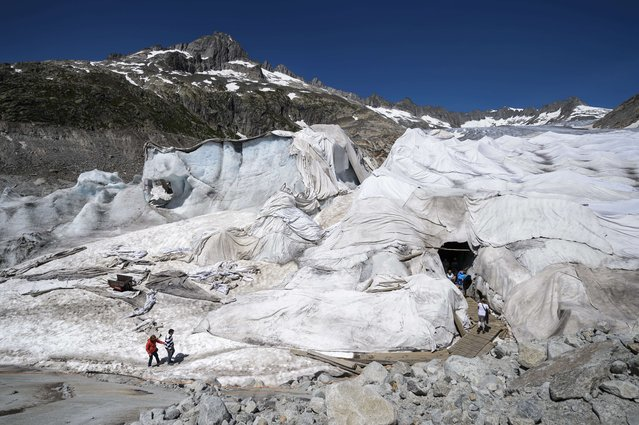 Tourists walk to visit an ice cave next to insulating foams wrapping up the Rhone Glacier which has been shrinking under the summer sun on July 14, 2015 near Gletsch. A second heat wave is forecast to hit Switzerland in the next few days. (Photo by Fabrice Coffrini/AFP Photo)