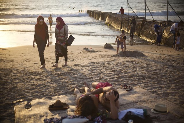 Muslim women stroll after bathing in the Mediterranean sea during the first day of the Eid al-Fitr holiday as the sun sets in Tel Aviv, Israel, Friday, July 17, 2015. (Photo by Ariel Schalit/AP Photo)