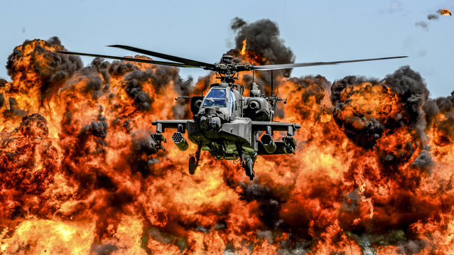 An AH-64D Apache attack helicopter flies in front of a wall of fire during the South Carolina National Guard Air and Ground Expo at McEntire Joint National Guard Base, South Carolina, U.S. on May 6, 2017. (Photo by Jorge Intriago/Reuters/Courtesy Air National Guard)