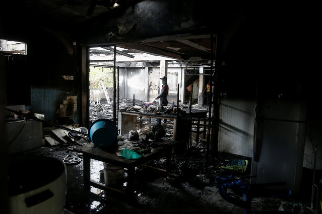 A forensic export inspects a burnt building at the Pitakkiat Wittaya School in the northern province of Chiang Rai, Thailand, May 23, 2016. (Photo by Athit Perawongmetha/Reuters)