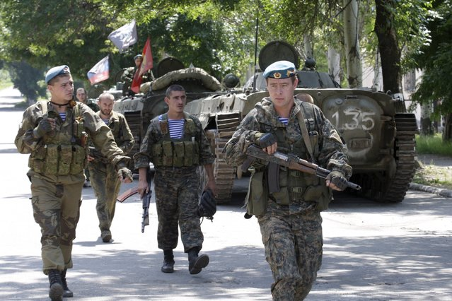 Members of the self-proclaimed Donetsk People's Republic forces walk past armoured personnel carriers (APC) near the urban settlement of Zaytsevo in Donetsk region, Ukraine, July 20, 2015. The Donetsk People's Republic (DNR) and Lugansk People's Republic (LNR) announced a unilateral three kilometers withdrawal of smaller weapons under 100mm calibre from the front line, according to local media. (Photo by Alexander Ermochenko/Reuters)