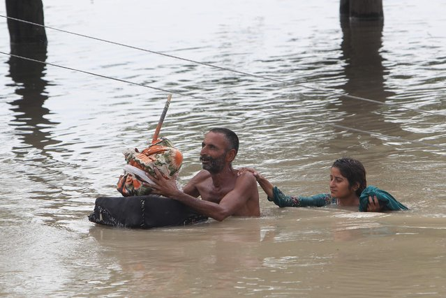 Pakistan villagers wade through floodwaters in Rajanpur, Pakistan, Pakistan, Thursday, July 23, 2015. The country's military has deployed helicopters and boats Wednesday to evacuate flood victims, as 285,000 have been affected by monsoon rains and flash floods in and around the city of Chitral in Pakistan's Khyber Pakhtunkhwa province, according to the National Disaster Management Authority. (Photo by Asim Tanveer/AP Photo)