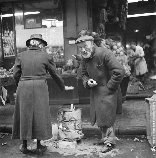 Two people warm themselves at a brazier on a street in the Soho area of London, 1947