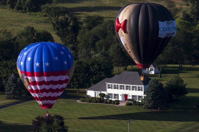 Hot air balloons land near a farmhouse as seen from a flying balloon just after sunrise on day one of the 2015 New Jersey Festival of Ballooning in Readington, New Jersey, July 24, 2015. (Photo by Mike Segar/Reuters)