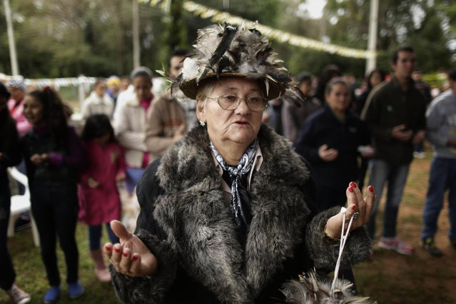 Dominga Mongelos prays during a Mass marking the feast day of St. Francisco Solano, in Emboscada, Paraguay, Friday, July 24, 2015. The religious festivity, that involves dressing up in bird-feather suits, was held in the patio of a chapel that bears the name of the saint, who was born in Spain in 1549 and died in Peru 1610. There is no record of the Spanish friar and South American missionary, also known as St. Francisco Solanus, in Paraguay, but the faithful believe in his miraculous powers. (Photo by Jorge Saenz/AP Photo)
