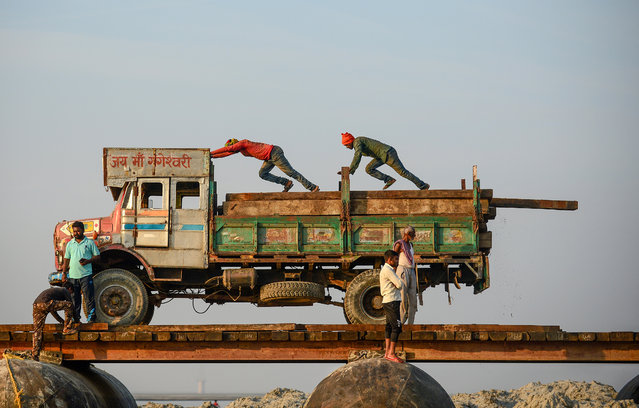 Labourers push wooden boards before carrying them to construct a temporary pontoon bridge over the Ganges river for the upcoming Hindu festival of Magh Mela in Allahabad on November 24, 2019. The Magh Mela is held every year on the banks of Triveni Sangam – the confluence of the three great rivers Ganga, Yamuna and the mystical Saraswati – in Allahabad during the Hindu month of Magh which corresponds to mid January – mid February. (Photo by Sanjay Kanojia/AFP Photo)