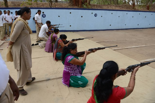 Indian instructors keep watch as participants fire .22 bore rifles during a five-day firearms training programme for women aged 15 and above at the Ahmedabad City Police firing range in Ahmedabad on June 17, 2014. The firearms training programme, organised by the Suraksha Setu initiative, a joint Gujarat state government, police, and rifle training club programme, aims to empower women aged 15 and above with self defence skills. Some 20,500 women across the state are expected to receive instruction in the initiative. (Photo by Sam Panthaky/AFP Photo)