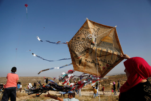 A Palestinian prepares to fly a kite during a festival organised by El Bireh municipality in the West Bank town of El Bireh June 1, 2016. (Photo by Mohamad Torokman/Reuters)