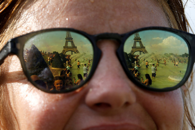 People cooling off in the Trocadero fountains across from the Eiffel Tower are reflected in sunglasses in Paris as a new heatwave broke temperature records in France, July 25, 2019. (Photo by Pascal Rossignol/Reuters)